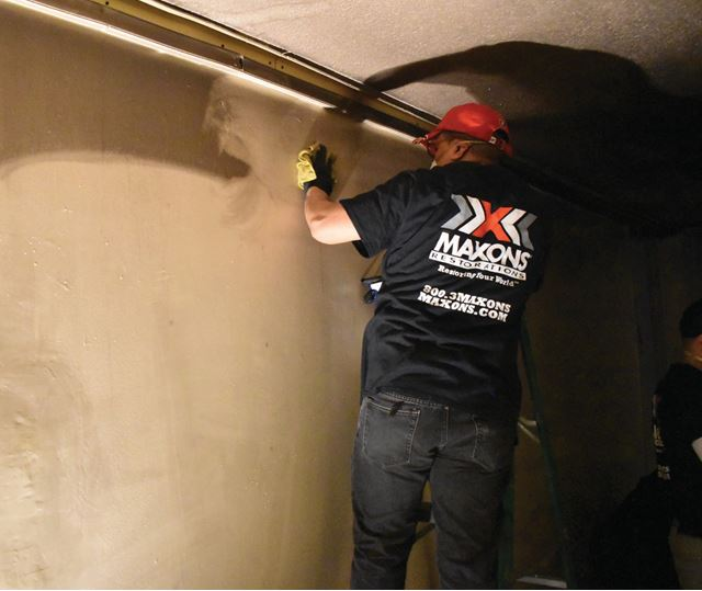 man cleaning soot from walls